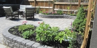 decorative stone wall with assorted perennials and black mulch