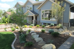 perennial bed with mow brick border decorative sandstone dry river bed and montane ground cover