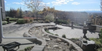 Borders - stackstone dry wall around dry river bed with cobble stone patio surrounding