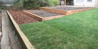 borders - pressure treated retaining wall and raised beds with cedar mulch and garden mix