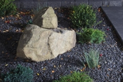 Borders - Charcoal pisa II retaining wall and revers a cap capstone, with rundle ground cover and assorted perennials.