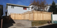 Fences - Cedar fence with decorative lattice top built on a combination of rustic pisa and capstone and 6 foot x 6 foot pressure treated retaining walls
