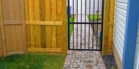 Gates - pressure treated fortress style fence with decorative iron gate