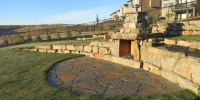 Stacked ironstone boulder retaining wall and outdoor fireplace with flagstone patio