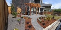 Patio Pathway - Charcoal rocky mountain pavers with tiered decorative pergola, composite deck landing and stairs cedar mulch and rundle beds