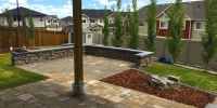 Patio - River rock paving stone in toscana with belvedere wall in copper canyon with dimensional coping in pacific grey