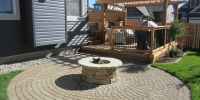 Cobblestone Patio with gas fed firepite, cedar deck and pergola
