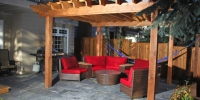 Decorative cedar pergola over seating area on barkman dimensional tiles.