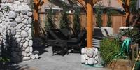 custom cedar pergola with river rock base