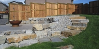 retaining wall - stackable ironstone slab retaining wall and steps with charcoal holland pavers and washed gravel beds