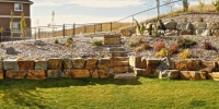 retaining wall - tiered stackable ironstone retaining wall with foothills alpine mulch beds and assorted perennials
