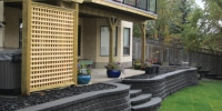 retaining wall - stacked armour stone with black mulch beds and pressure treated privacy screen and pergola