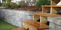 Wooden steps integrated into stone retaining wall