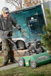 man using a power raker with trailer behind him