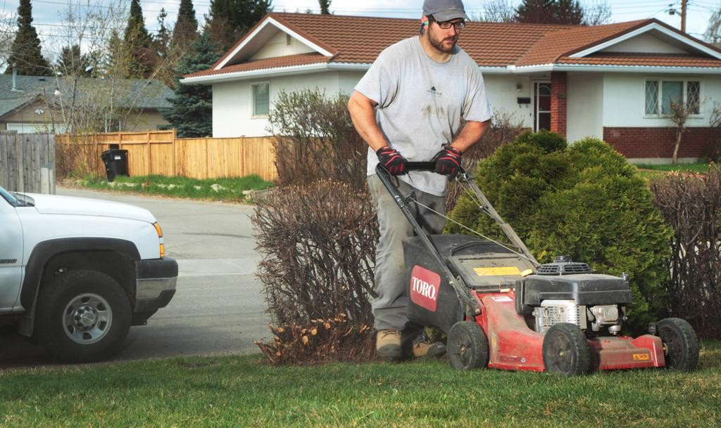 man in work clothes pushing lawn mower