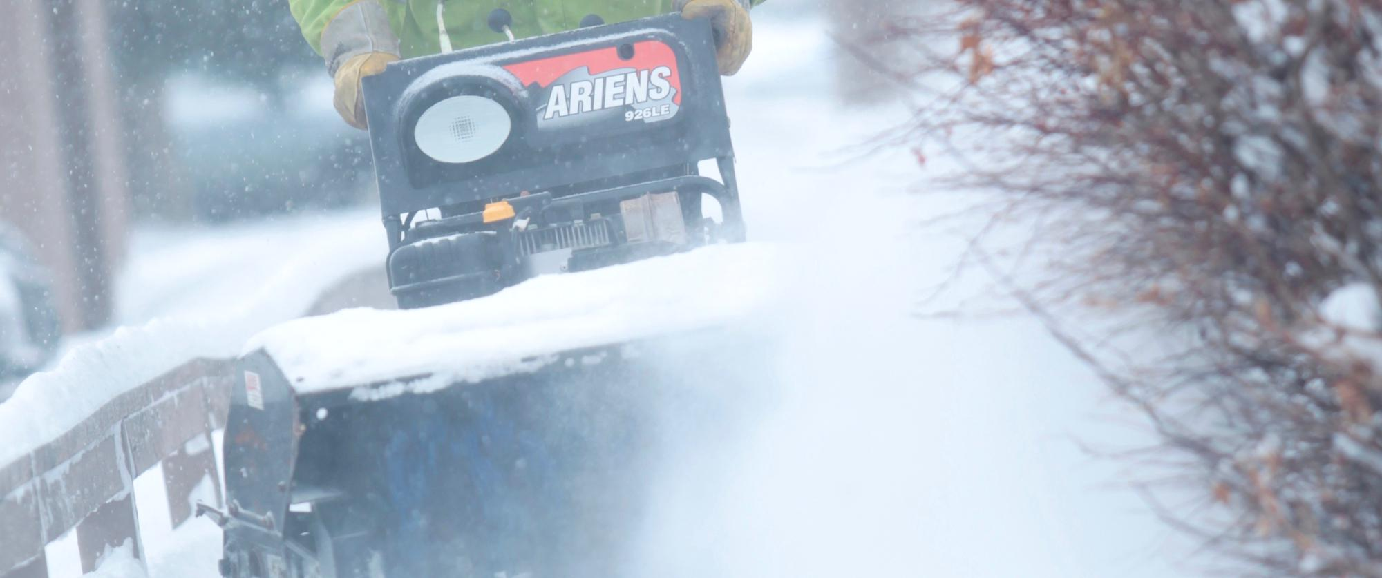 Clearing residential sidewalks with a snow blower
