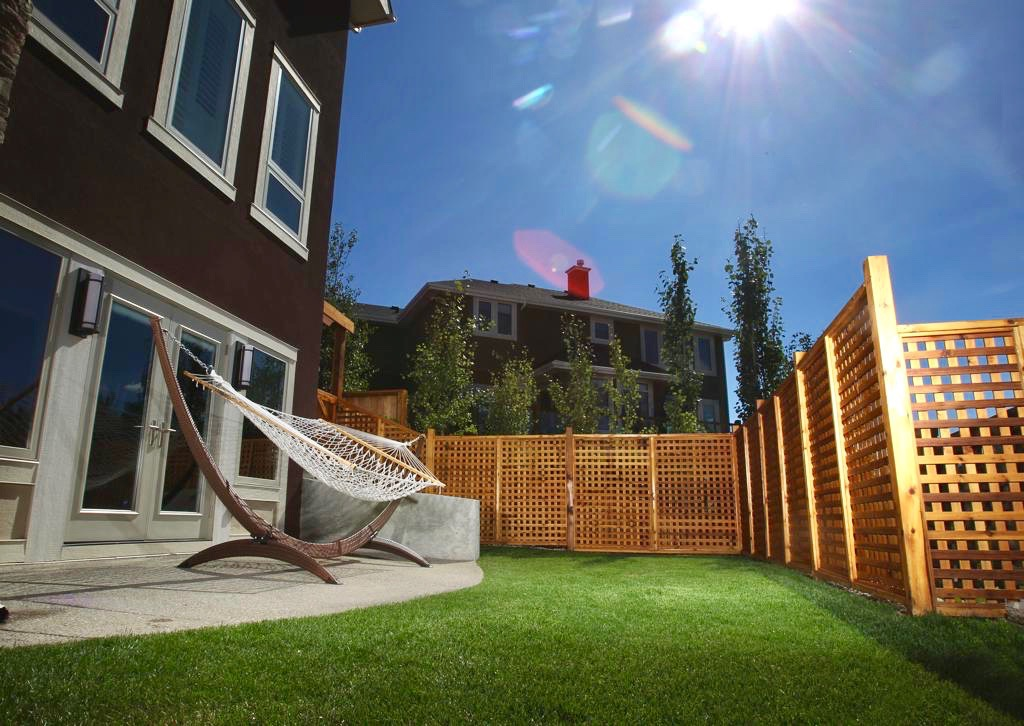 stained cedar lattice fence in a calgary backyard