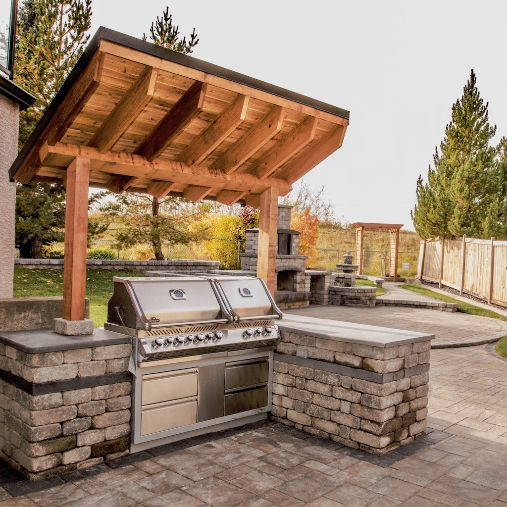 outdoor kitchen with a bbq and fireplace built with paving stones