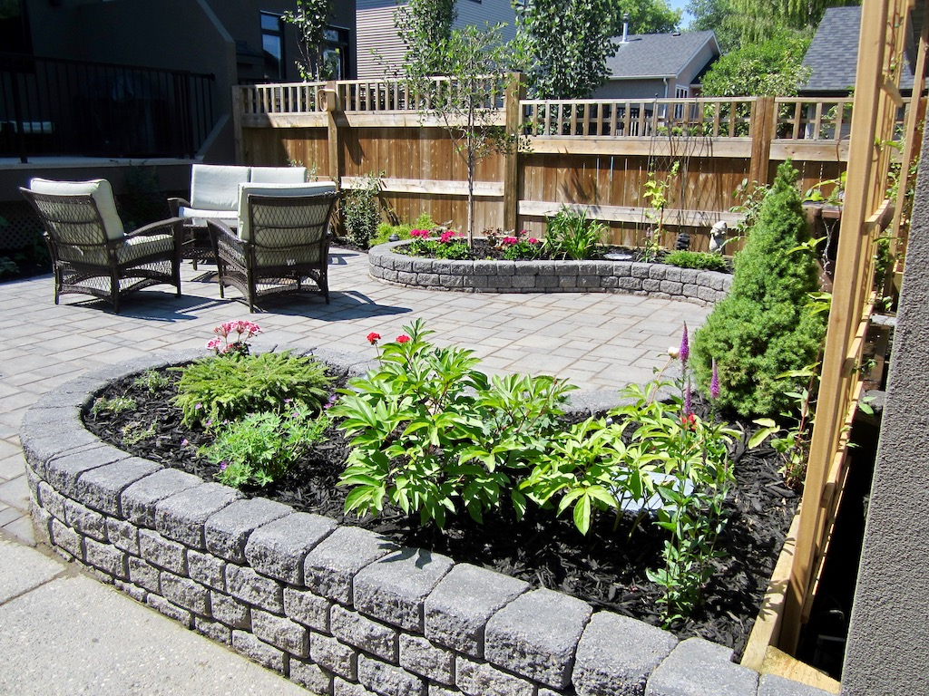 Planting in raised stone garden beds in a private backyard