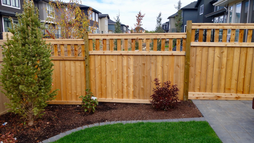 Wood style fence with decorative lattice top in a backyard