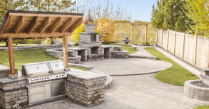 backyard landscape with paving stone patio outdoor kitchen and fireplace