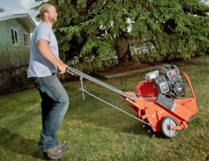 man aerating front lawn with a core aeration machine