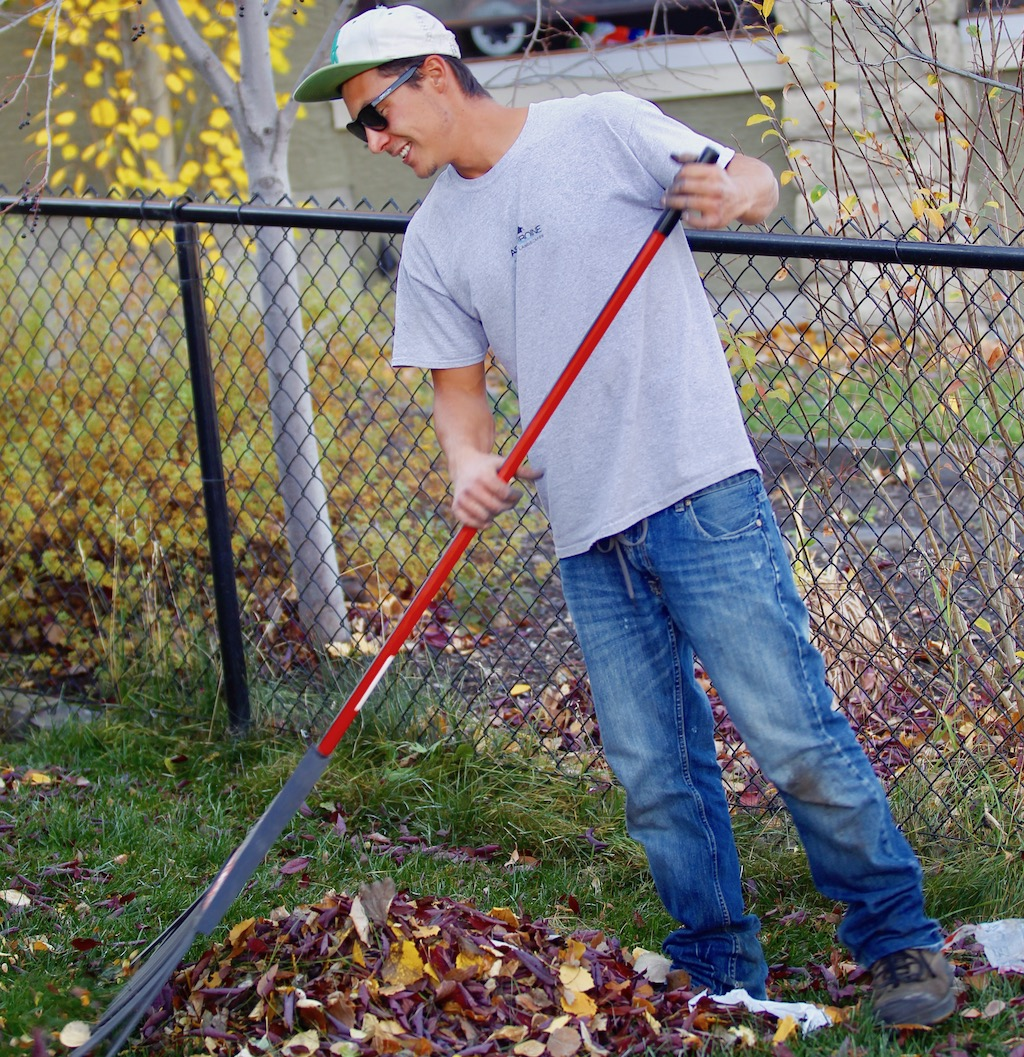young man raking leaves into a pile