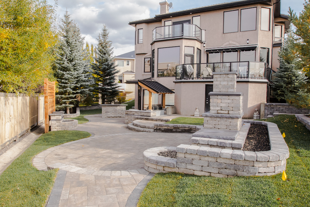 fully landscaped back yard with paving stone patio, raised stone bed and a stone fire place feature